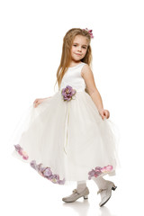 6 years old girl in princess dress making curtsy