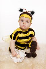 Baby earing bee costume sitting on the floor