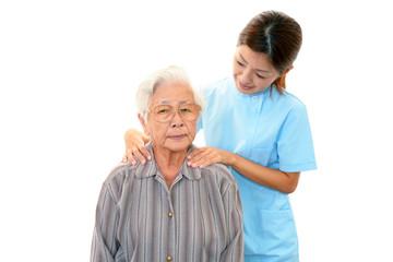 高齢者の肩もみをする笑顔の介護士