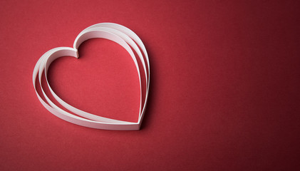 White paper heart on the red with copy space