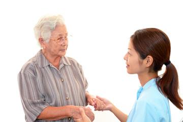 手を取り合い微笑む高齢者と介護士
