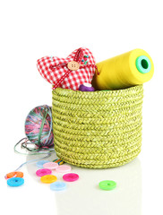 Green wicker basket with accessories for needlework isolated