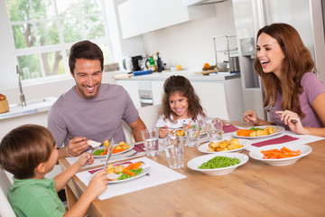 Wall Mural - Family laughing around a good meal