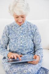 Elderly focused woman using a digital tablet