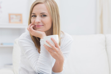 Portrait of woman with tea cup at home