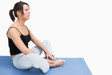 Side view of woman sitting in yoga position on exercise mat