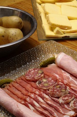 Raclette cheese with meats (ham, sausage) and potatoes