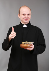 Young pastor with money on gray background