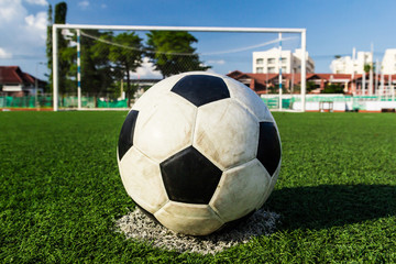 soccer ball on green grass in front of goal net