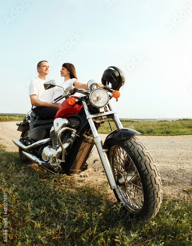 Fototapete Young biker couple on the country road