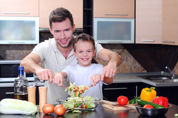 Little boy and his father cooking in the kitchen