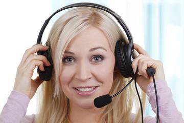 Callcenter Angestellte setzt Headset auf