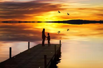 Fotorolgordijn Pier madre e hijo disfrutando de la puesta de sol