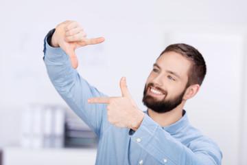 lächelnder mann schaut durch fingerrahmen