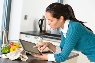 Young woman reading recipe tablet kitchen searching