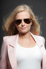 Blonde girl with long hair and sunglasses. Beauty studio shot.