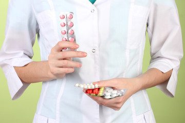 Close-up of female doctor hand holding pills,