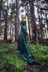 wild beauty blonde woman long green dress in the forest