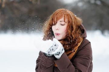 Outdoors portrait of young beautiful woman having fun in winter