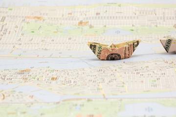 USD Geldschein als Papierschiff auf Landkarte