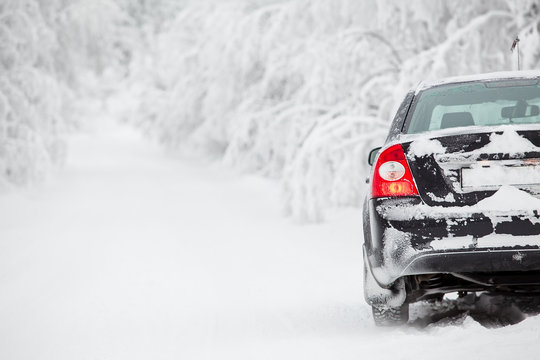 Black land vehicle standing on winter road on roadside