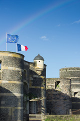 Towers of castle of Angers under rainbow, France and EU banners
