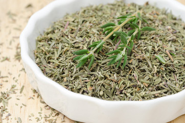 Dried and fresh thyme in a white bowl, selective focus, closeup