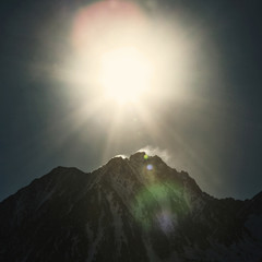 Sun shining on snow covered montain