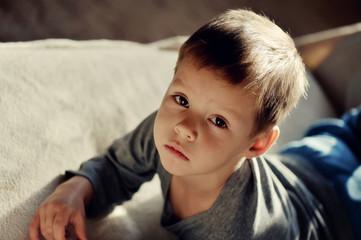 on the sofa lay a little boy in the sun than the upset
