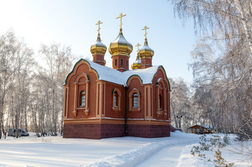 Orthodox chapel in a snowy winter forest