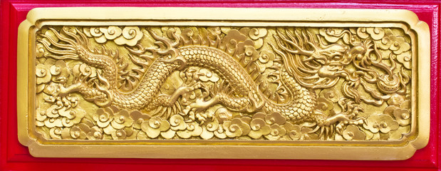 Golden dragon(Chinese: Long) wood carving in Red background