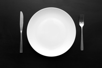 empty white plate with fork and knife on dark wooden table