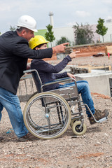 Architect shows disabled woman in wheelchair construction sites