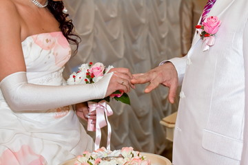 The bride and groom wear each other rings