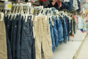 Trousers and jeans on stands in kids store