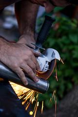 Hombre cortando caño de hierro con amoladora.
