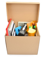 Cardboard box full of office supplies isolated on white