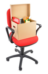 Cardboard box full of office supplies on chair