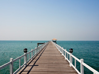 wooden bridge to the sea in sunny day