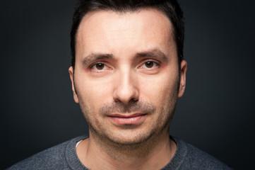 Man close up portrait against dark background.