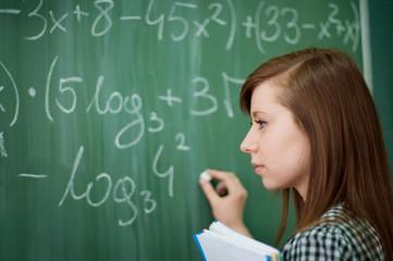 Student girl writing mathematical formula