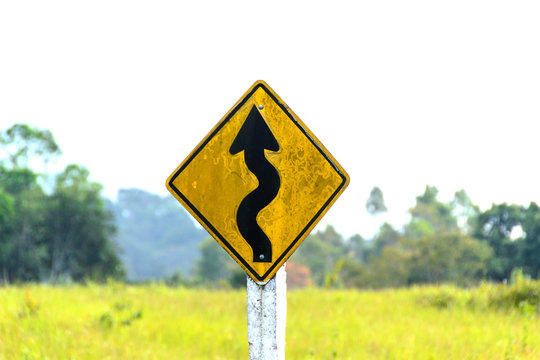 winding road sign in yellow