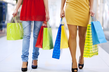 Low section of young friends carrying shopping bags