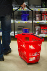 Customer with small red rolling basket select goods in supermark
