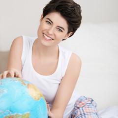lächelnde frau schaut auf globus