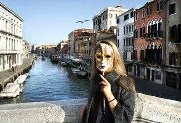 Woman in beautiful Venetian mask in Venice