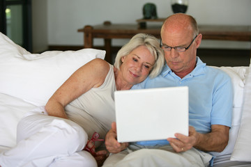 Middle-aged couple sat on sofa with laptop