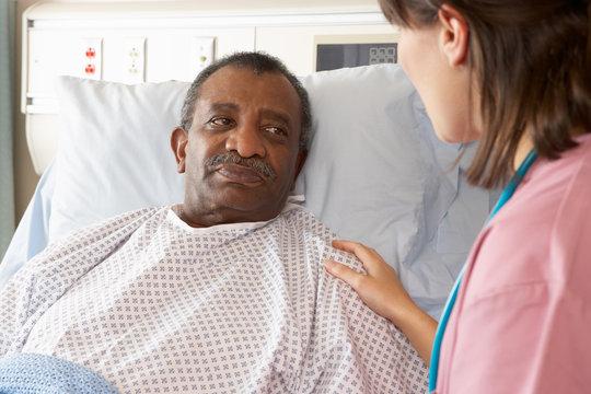Nurse Talking To Senior Male Patient On Ward