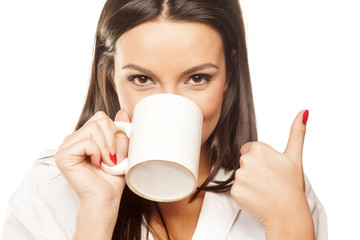 smiling beautiful girl drinking tea and shows thumb