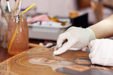 restorer cleaning ancient icon